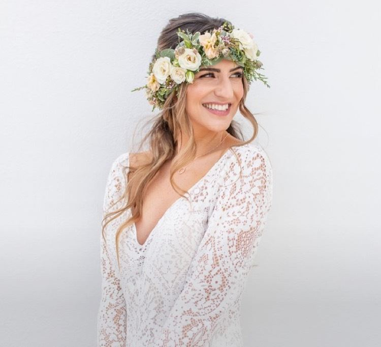 Model wearing a boho wedding dress with a flower crown shown on a mobile device