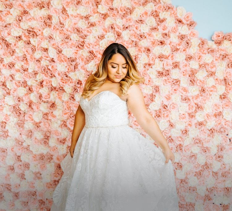 Model wearing white wedding dress standing in front of a rose wall shown on mobile device